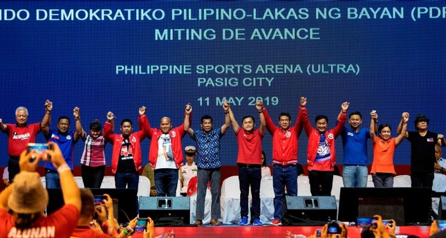 Philippine President Rodrigo Duterte (C) raises the hands of senatorial candidates during the Partido Demokratiko Pilipino-Lakas Bayan (PDP-LABAN) in Manila on May 11, 2019 ahead of the mid-term elections on May 13. (AFP Photo)