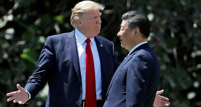 In this Friday, April 7, 2017, file photo, U.S. President Donald Trump, left, gestures as he and Chinese President Xi Jinping walk together at Mar-a-Lago in Palm Beach, Florida. AP Photo
