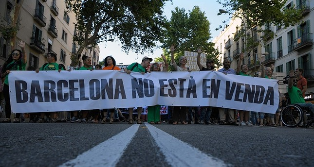 Protesters holds a placard that says: Barcelona is not for sale  during a demonstration in Barcelona on June 10, 2017 against what they claim is a lack of control by the city's tourism management. (AFP Photo)