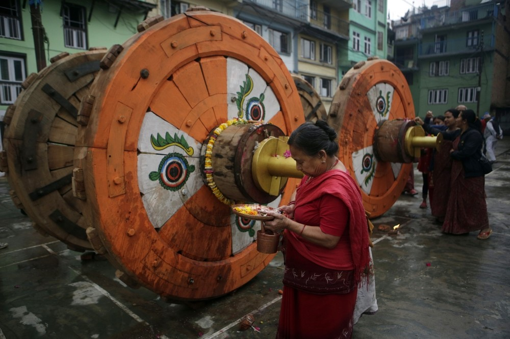 A Hindu woman performs ritualss in front of wheels that will be assembled for the Rato Machindranath Chariot.