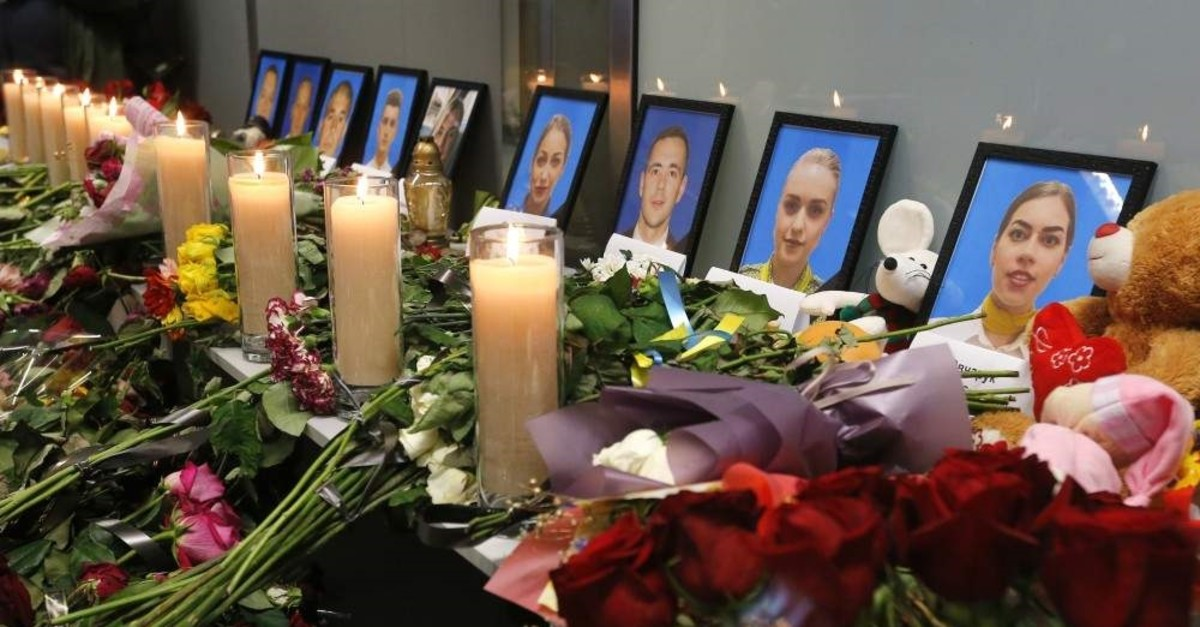 Flowers and candles are placed in front of portraits of the flight crew members of the Ukrainian 737-800 plane that crashed on the outskirts of Tehran, at a memorial inside Borispil International Airport outside Kyiv, Ukraine, Saturday, Jan. 11, 2020. (AP Photo)
