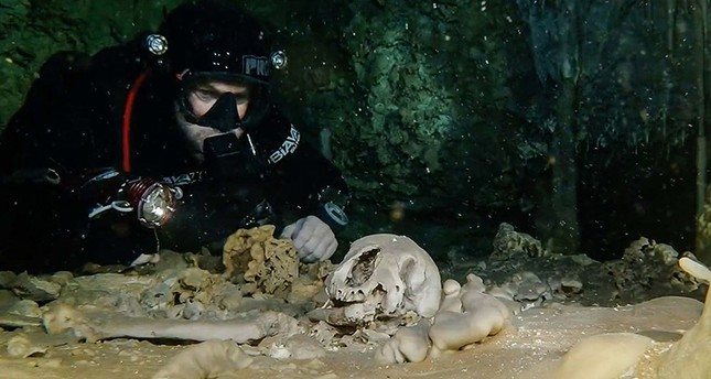 This undated photo released by Mexico's National Anthropology and History Institute (INAH) shows a diver looking at human remains believed to be from the Pleistocene era, in the Sac Actun underwater cave system near Tulum, Mexico. (INAH via AP)