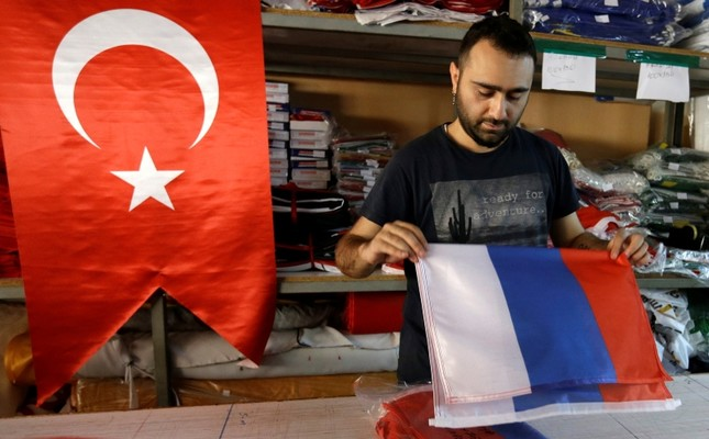 An employee of a flag-making factory folds a Russian flag as a Turkish flag adorns the display at left, in Istanbul, Tuesday, Aug. 9, 2016. AP Photo