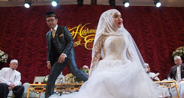 A newly married woman and her husband (2nd L) get ready to pose for a portrait during their wedding reception at the Al Meroz hotel in Bangkok.