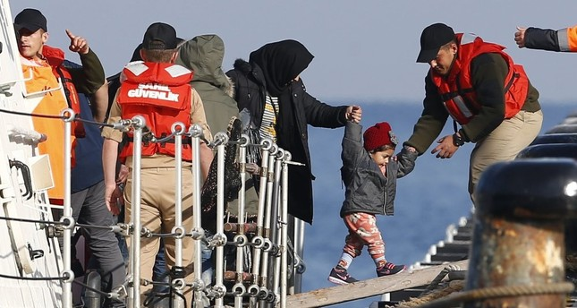 Migrants disembark from a Coast Guard boat after their boat was intercepted in the Aegean town of Dikili.