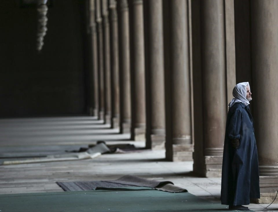 A Muslim man looks out from a mosque.