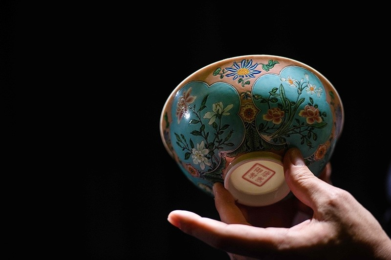 Nicolas Chow, deputy chairman for Sotheby's Asia, holds an extremely rare Qing Dynasty bowl  (AFP Photo)