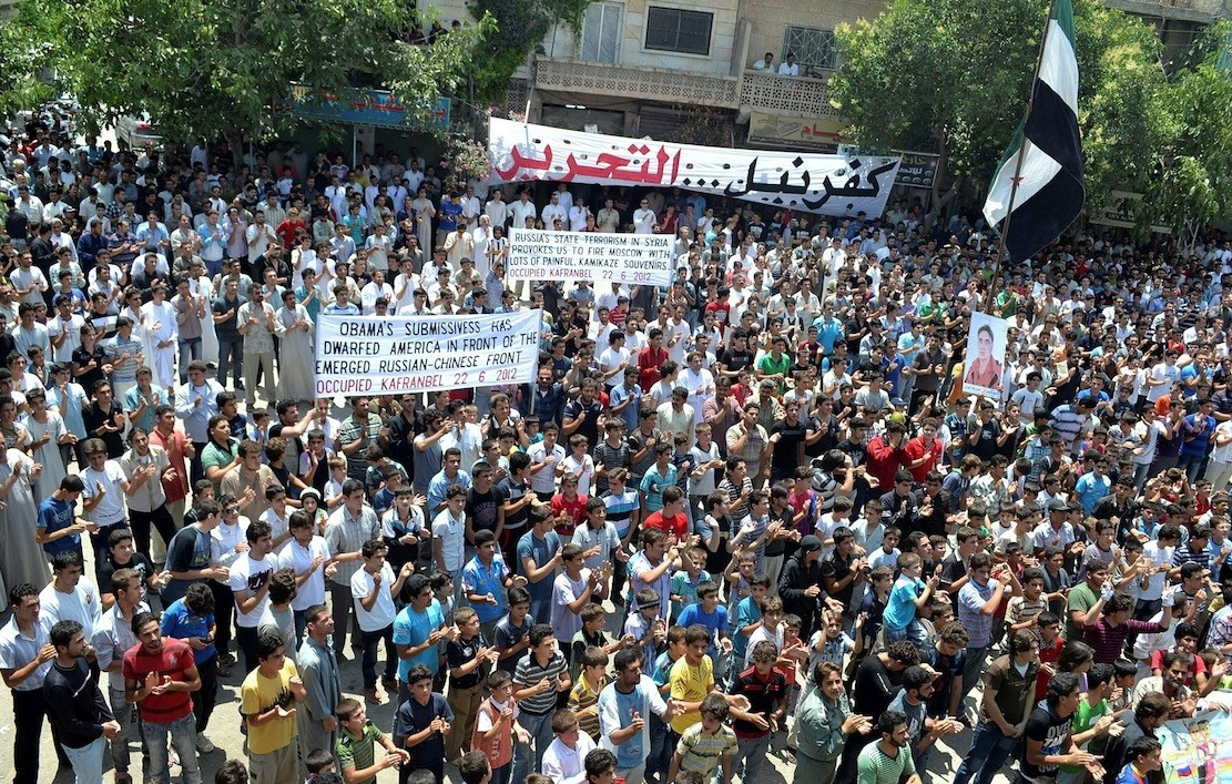 A handout image released by the Syrian opposition's Shaam News Network shows anti-regime demonstrators holding banners and clapping during a protest in Kfar Nubul, in the northern province of Idlib, on June 22, 2012.