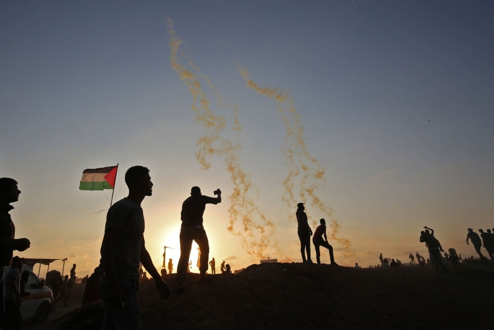 Palestinian civilians protest as tear gas is fired by Israeli troops, near the border with Israel, southern Gaza Strip, May 15.