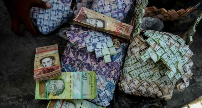 Wilmer Rojas, 25, shows the purses he makes, using Bolivar bills in Caracas.