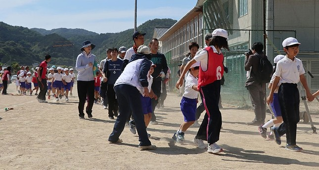 Schoolchildren are led by teachers toward a gymnasium during an evacuation drill at the Abu elementary school in Abu town, Yamaguchi prefecture. (AFP Photo)