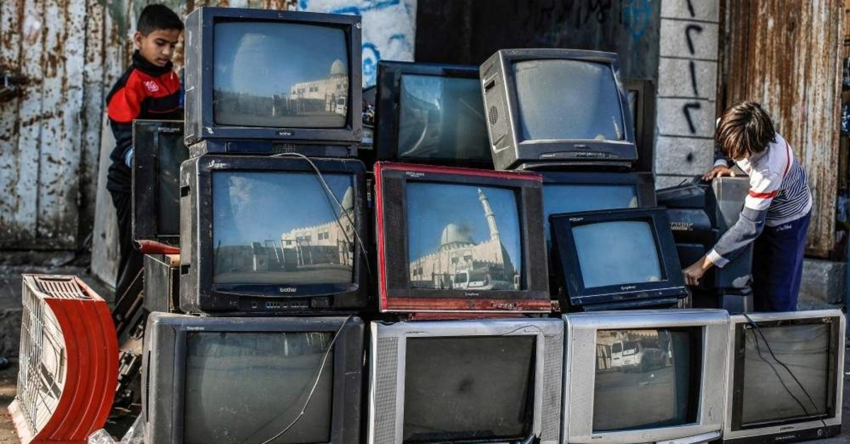 Palestinian children play with old CRT television sets displayed along a street near their home at al-Shati refugee camp in Gaza City, Dec. 6, 2019. (AFP)