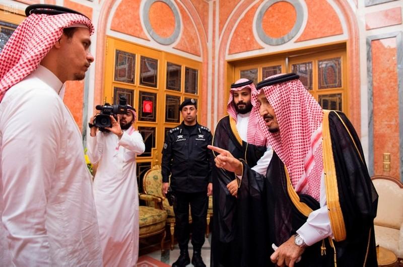 Saudi King Salman, right, points to Salah, a son of Jamal Khashoggi as Crown Prince Mohammed bin Salman, second right, looks on, in Riyadh, Saudi Arabia, Oct. 23, 2018.