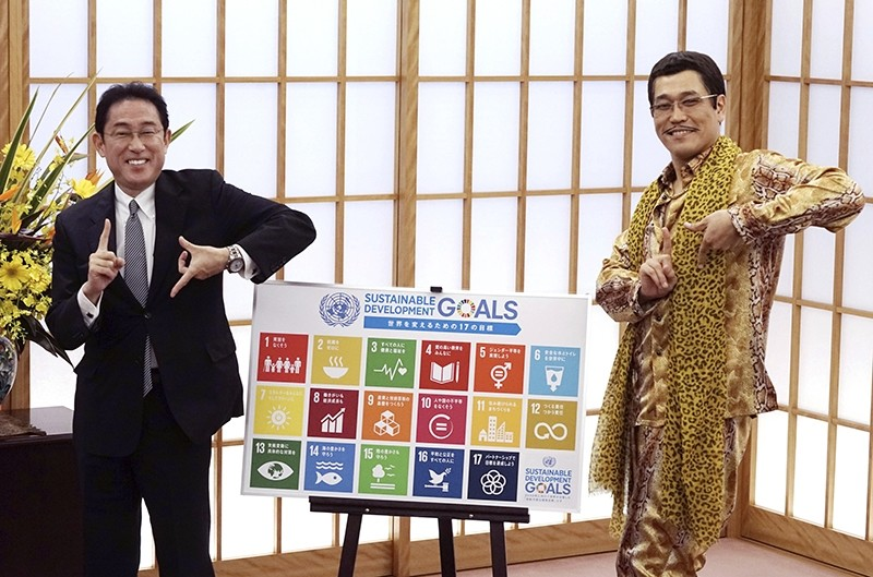 Japanese comedian Pikotaro, right, and Japan's Foreign Minister Fumio Kishida pose to raise awareness about the United Nation's 17 Sustainable Development Goals (SDGs) at the ministry in Tokyo, Wednesday, July 12, 2017. (AP Photo)