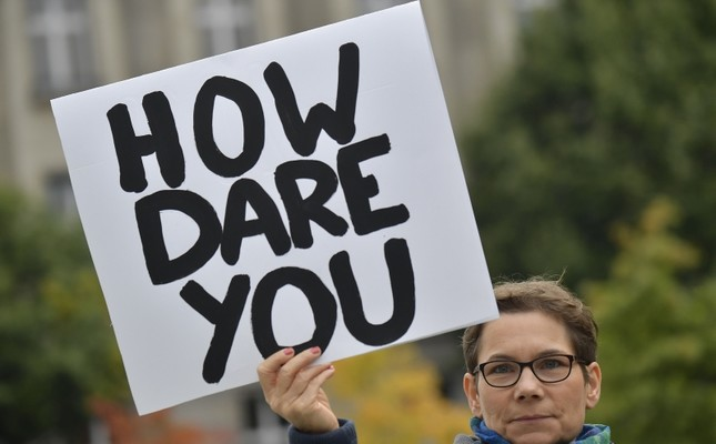 An environmentalist holds up a poster reading How dare you, quoting Swedish teenage climate activist Greta Thunberg, as she protests outside the German Chancellery where is taking place the weekly cabinet meeting in Berlin AFP Photo