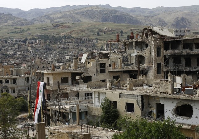 A Syrian national flag hangs off a damaged building at the mountain resort town of Zabadani in the Damascus countryside, Syria, May 18.
