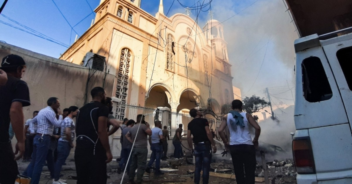 People gather at the scene of a car bomb explosion outside a church in the predominantly-Kurdish city of Qamishli in northeast Syria on July 11, 2019. (AFP Photo)