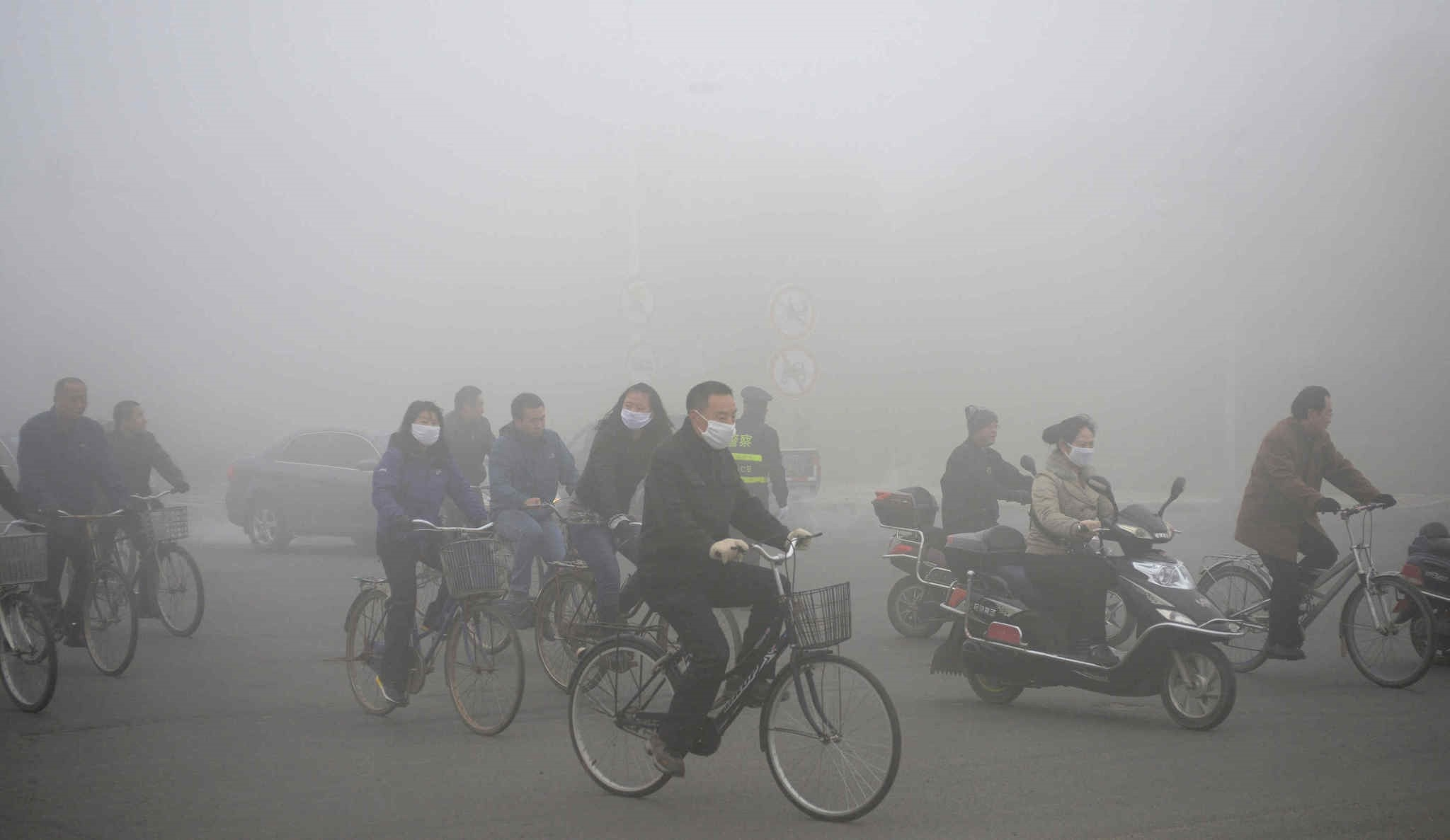 People ride along a street on a smoggy day in Daqing, Heilongjiang province of China.