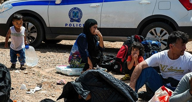 Refugees and migrants sit on the ground by a Greek police car upon their arrival with a boat near the village of Finokalia in the southern Greek island of Crete on May 31, 2016. (AFP Photo)
