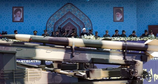 A vehicle carryingan Iranian medium range missile passes by President Rouhani during the annual military parade on Friday.