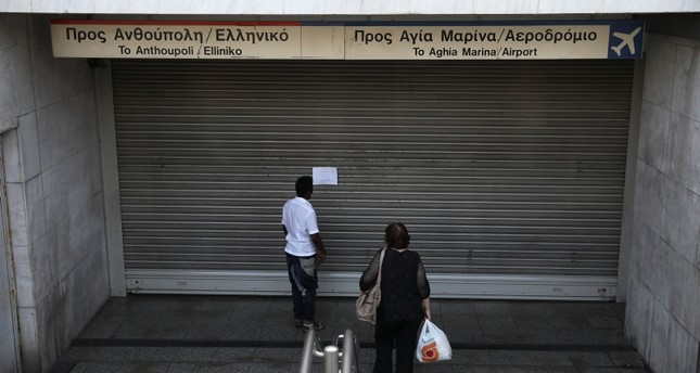 People read an announcement at a closed metro station, during a 24-hour general strike in Athens, Greece, Oct. 2, 2019. (Reuters Photo)