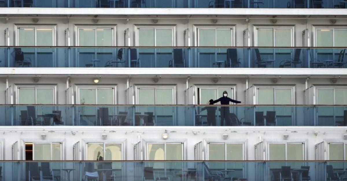 A passenger stands on the balcony of the cruise ship Diamond Princess anchored at the Yokohama Port in Yokohama, near Tokyo Friday, Feb. 7, 2020. Japan. (AP Photo)