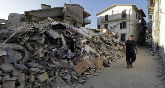 A man walks by rubble in the village of Santi Lorenzo e Flaviano, central Italy.