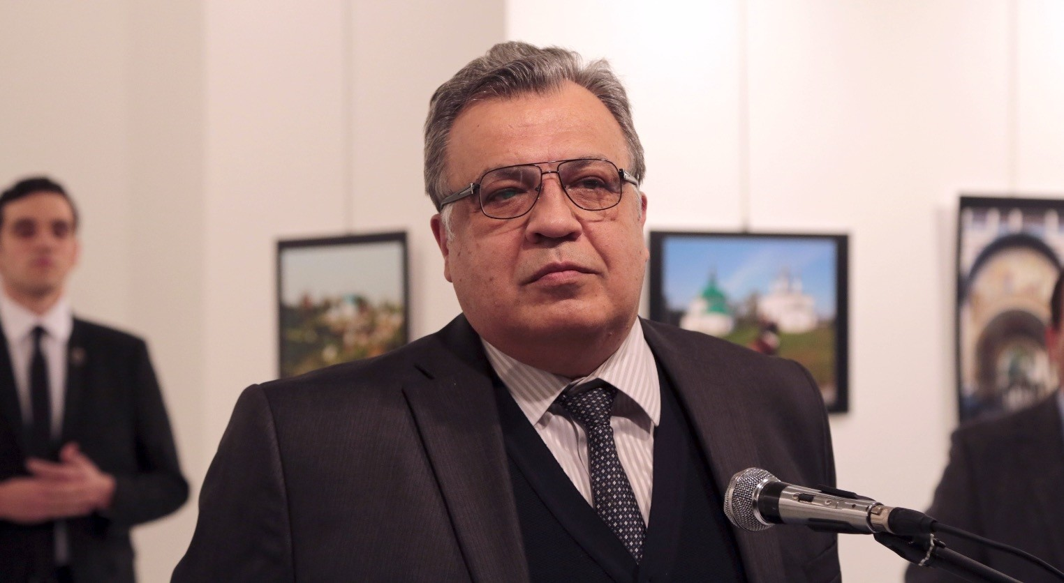 The Russian Ambassador to Turkey Andrei Karlov speaks at a gallery in Ankara Dec. 19, 2016. The gunman is seen in the back left of the photograph.