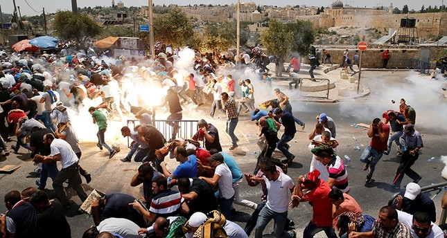 Palestinians react following tear gas that was shot by Israeli forces after Friday prayer on a street outside Jerusalem's Old city July 21, 2017. (Reuters Photo)