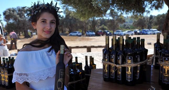 A girl holds a half-liter bottle of olive oil in Seferihisar, Izmir on Oct. 16, 2017. (AA Photo)