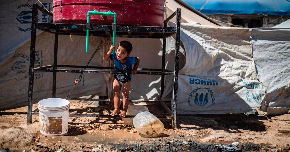 A displaced Syrian boy drinks water from a tank at the al-Hol camp for the internally displaced people in al-Hasakeh governorate in northeastern Syria, July 23, 2019.