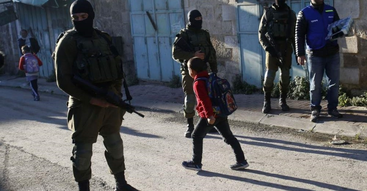 Palestinian children walk past Israeli soldiers on their way to school in the West Bank city of Hebron, Feb. 12, 2019.  (AP Photo)