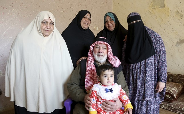 From left to right (standing): Bassama Abu Massoud,72; her daughter Hanaa,50; Hanaa's daughter,Abir,33; Abir's daughter, Ala,18. Patriarch Abdullah Abu Massoud,77, sits in a chair, holding his 9-month-old great-great-granddaughter, Tuqaa, in his lap.