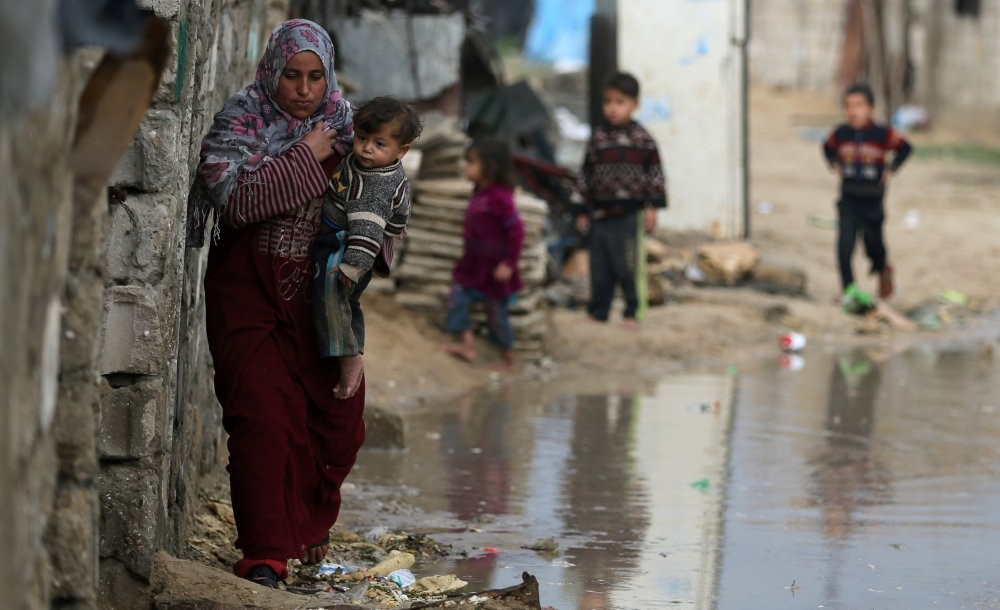 A Palestinian woman carrying her child walks on a rainy day in the southern Gaza Strip, Dec. 30.
