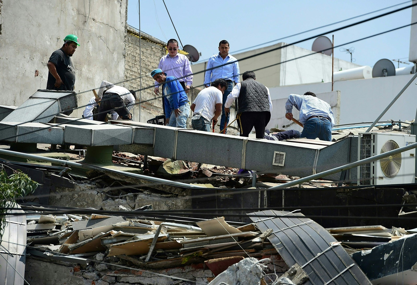 People look through debris of a building which collapsed when  quake rattled Mexico City on September 19, 2017. (AFP Photo)