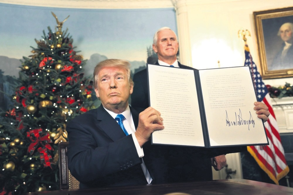U.S. Vice President Mike Pence (R) watches as President Trump holds up his proclamation about his controversialdecision to recognize Jerusalem as the capital of Israel, at the White House, Washington, Dec. 6.