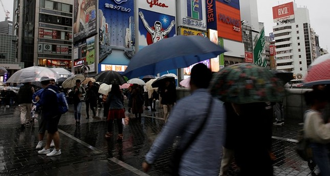Shoppers walk under umbrellas as Typhoon Lan approaches Japan's mainland, in Osaka, western Japan, October 22, 2017. (Reuters Photo)