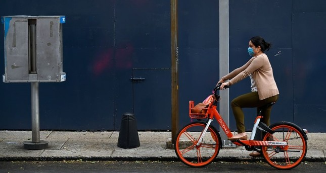 A woman rides a bike wearing a face mask in Mexico City, May 17, 2019.