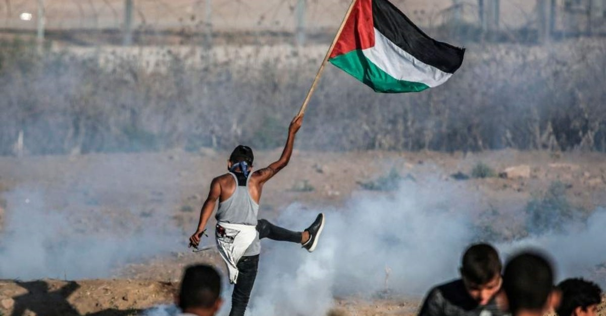 A protester raises a Palestinian flag during clashes with Israeli forces across the border, Gaza Strip, Sept. 6, 2019. (AFP Photo)