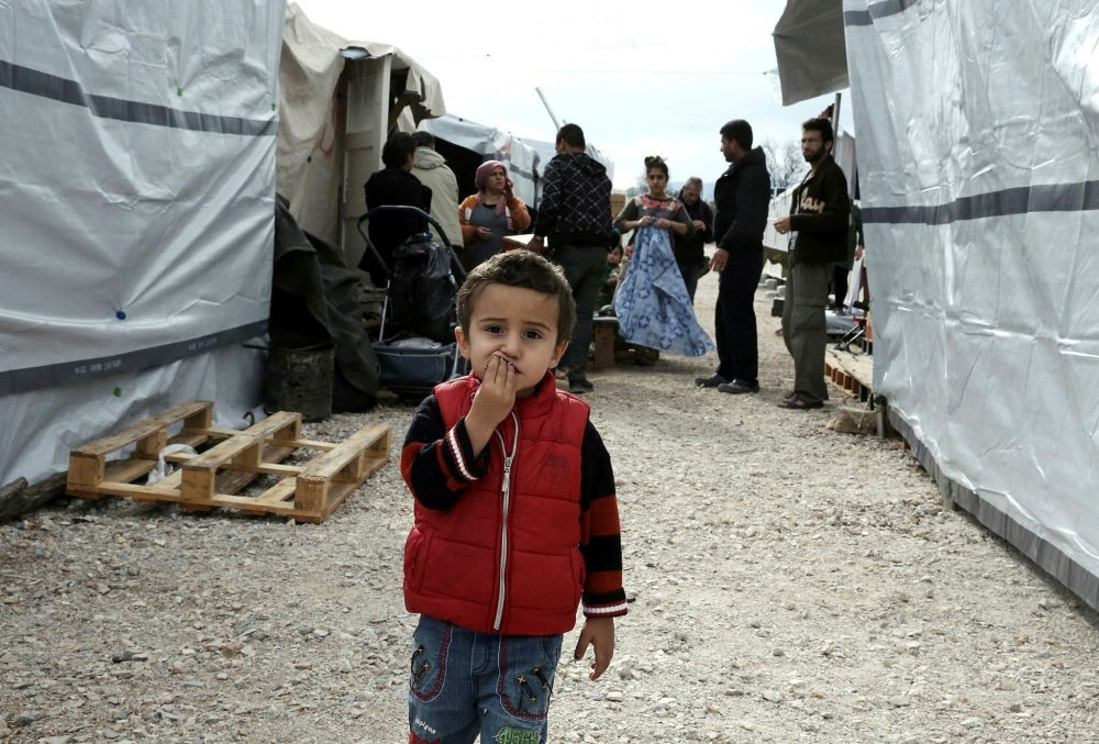 A Syrian refugee child stands outside tents at the refugee camp in Ritsona, north of Athens, Greece.