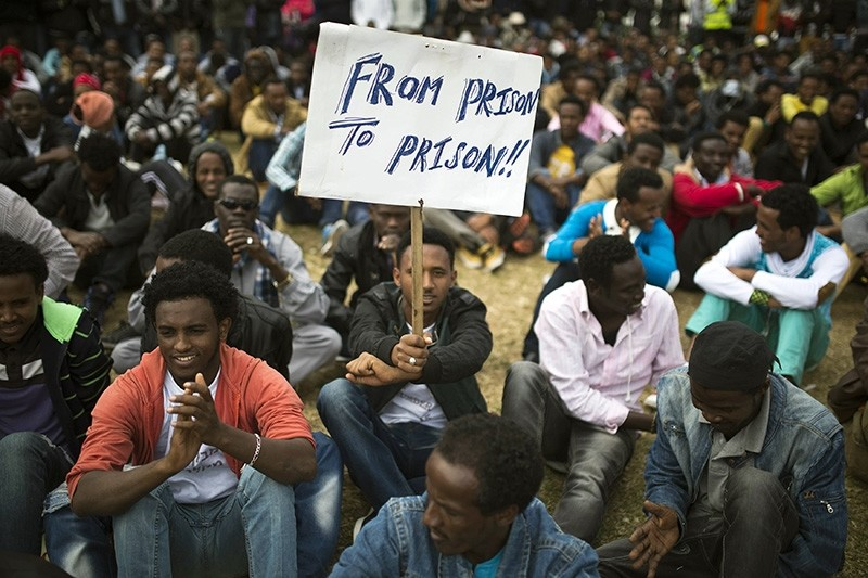 An African migrant holds a placard at Tel Aviv's Levinsky park, January 9, 2014, on the fifth consecutive day of protests against Israel's detention policy toward migrants it sees as illegal job-seekers. (Reuters Photo)