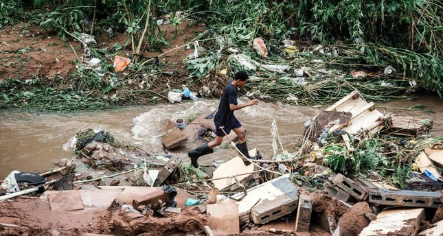 A man tries to retrieve some of his furniture at an informal settlement of BottleBrush, south of Durban, after torrential rains and flash floods destroyed his home on April 23, 2019. (AFP Photo)
