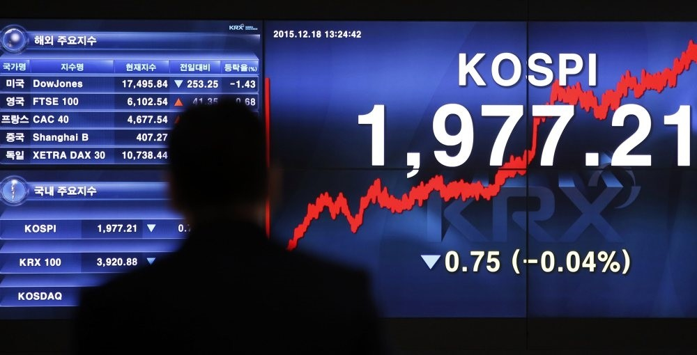A man looks at an electronic screen showing the Korea Composu0131te Stock Price Index (kospu0131) and foreign stock price index in Seoul. (AP Photo)