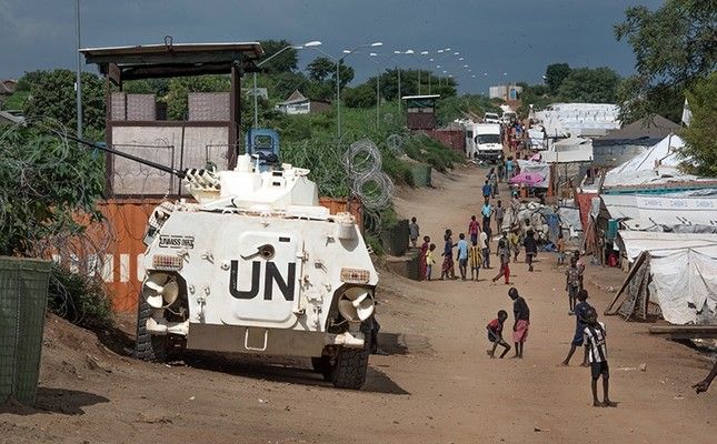 Some of the more than 30,000 Nuer civilians sheltering in a UN base in South Sudan's capital Juba for fear of targeted killings by gov't forces walk by an armored vehicle and a watchtower manned by Chinese peacekeepers, July 25, 2016. (AP Photo)