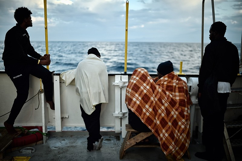In this file photo taken on May 14, 2018 migrants look at the coastline as they stand aboard the French rescue ship MV Aquarius, off the coast of Sicily. (AFP Photo)