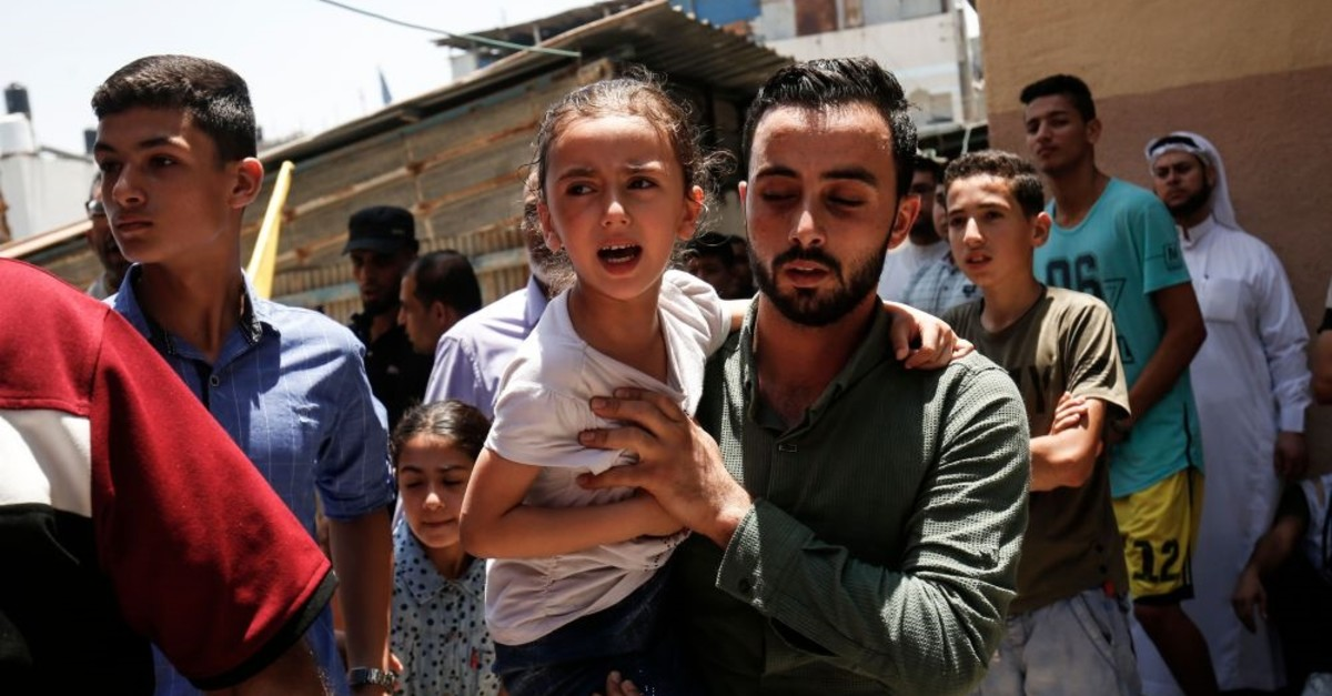 Mirfat, the daughter of paramedic Mohammed al-Jdaili, mourns during her father's funeral in the central Gaza Strip on June 11, 2019.