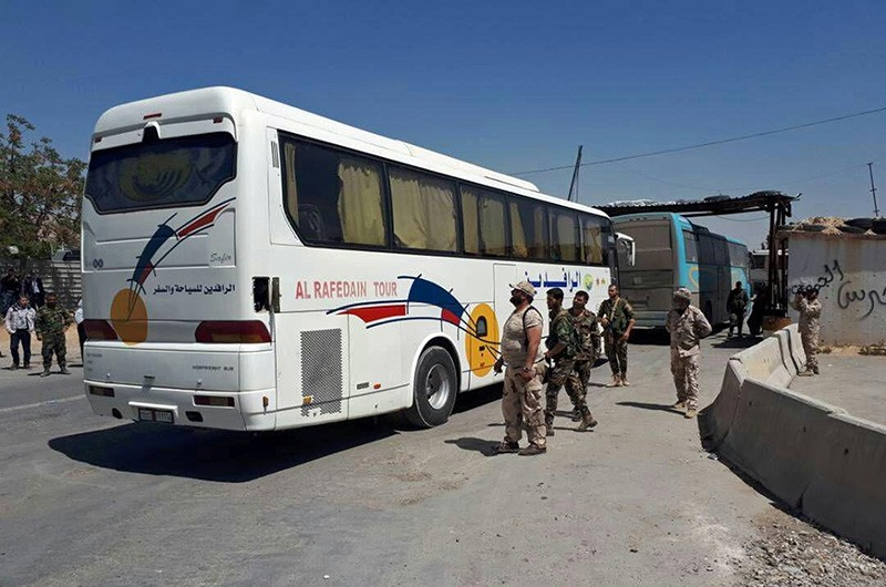 This photo released by the Assad regime news agency SANA, shows regime forces overseeing the evacuation by bus of Army of Islam fighters from the besieged town of Douma, just east of Damascus, Syria, Monday, April 2, 2018. (AP Photo)