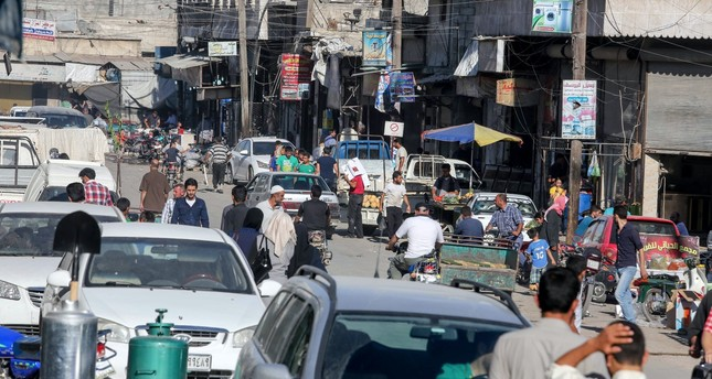 Syrians walk on the streets in the city of Azaz on Syria's northern border with Turkey.