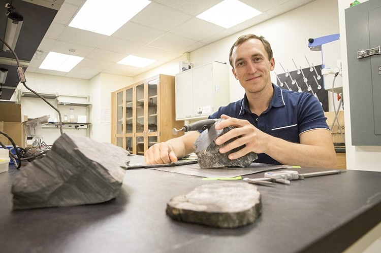 Erik Gulbranson, paleoecologist and visiting assistant professor at UWM, studies some of the fossilized trees he brought back from Antarctica. (UWM Photo/Troye Fox)