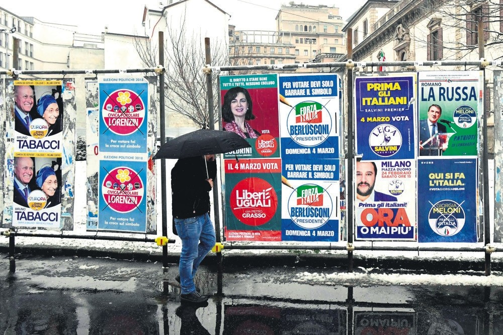 A pedestrian passes in front of election posters prior to the Italian elections, Milan, March 1.